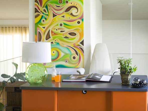 Sleek orange office desk with colorful art